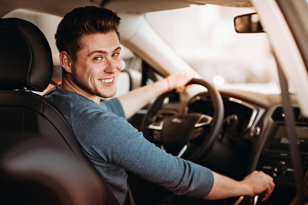 man in car smiling at camera with hand on shifter